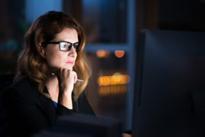 Woman examines computer screen